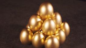 Het roteren van gouden eieren op zwarte achtergrond stock video