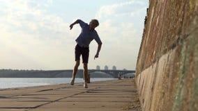 Het rots-n-Broodje van jonge Mensendansen op een Riverbank met een Hoge muur in de Zomer stock footage