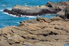 Het rotsachtige strand van Oregon op blauwe vreedzaam stock afbeeldingen