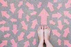 Het roze Concept van de Pijlkeus Vrouwelijke Naakte Voeten met Roze Nagellakmanicure Status en Vele Keuzen van Richtingspijlen op Royalty-vrije Stock Foto's