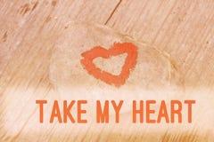 Het roze die hart met lippenstift op stuk van steen op achtergrond van houten raad met tekst wordt geschilderd neemt mijn hart stock afbeelding