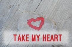 Het roze die hart met lippenstift op stuk van steen op achtergrond van houten raad met tekst wordt geschilderd neemt mijn hart royalty-vrije stock afbeelding