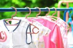 Het roze en gekleurde babywasserij hangen op een drooglijn Stock Fotografie