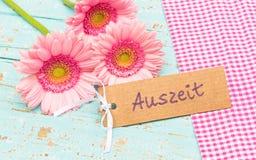 Het roze gerberamadeliefje bloeit en etiket met Duits woord, Auszeit, middelenonderbreking royalty-vrije stock foto