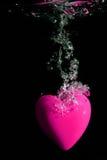 Het roze hart bespatten op water Stock Foto