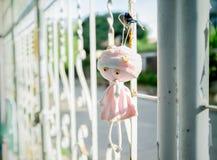 Het roze pop hangen op de omheining Zeer droevig het Stock Fotografie