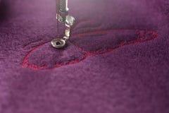 het roze vlinderborduurwerk op purpere gekookte wol - eerste wordt uitgevoerd vleugel - bekijkt op machinevoet in heldere backlig royalty-vrije stock foto's