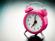 Het roze wekker bellen stock foto's