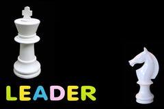 Het rubber van de alfabetspons van tekst 'LEADER 'met van het schaakkoning en paard status geïsoleerd over zwarte achtergrond Zak royalty-vrije stock foto