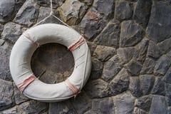 Het rubber van de het levensbesparing, Reddingsboei het hangen op rotsmuur Stock Afbeeldingen