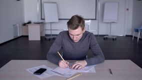 In het ruime gebruik van de bureauspecialist een potlood om een document lay-out te trekken stock video