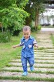 Het runnen van weinig kindjongen op aard Stock Foto's