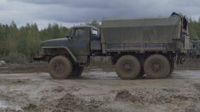 Het Russische de vrachtwagen van het legerpersoneel drijven bij de landweg stock video
