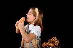 Het Russische meisje die ongezuurde broodjes eten en drinkt thee van a stock fotografie
