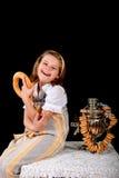 Het Russische meisje die ongezuurde broodjes eten en drinkt thee van een samovar royalty-vrije stock foto