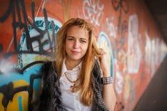 Het Russische mooie glimlachende tienermeisje met lang blond haar en maakt omhoog dichtbij de muurgraffiti, selectieve nadruk Stock Afbeeldingen