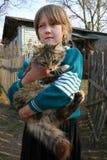 Het Russische oude plattelandsmeisje 8 jaar, houdt grote ruwharige kat Stock Foto