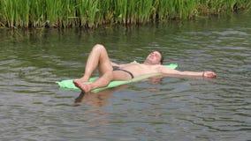 Het rusten van de Man in de Hete de Zomerdag die in de Rivier zwemmen op de Matras stock footage