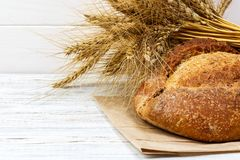Het rustieke brood en de tarwe op een oude wijnoogst planked houten lijst Donkere humeurige achtergrond met vrije tekstruimte vri royalty-vrije stock foto's