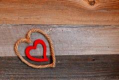 Het rustieke hart van Valentine ` s op achtergrond van doorstaan hout Stock Foto