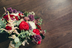 Het rustieke huwelijksboeket met rood nam en lilac bloemen op houten toe Stock Foto's