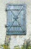 Het rustieke oude blind van het metaalvenster op een oude huisvoorzijde stock afbeelding