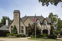 Het rustieke rots en baksteen prachtig gemodelleerde huis voor de betere inkomstklasse met koperspitsen en schoorsteen behandelt  stock fotografie