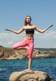 Het rustige jonge vrouw blijven op de rotsachtige kust in yoga stelt Stock Foto's