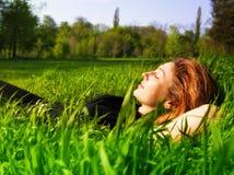 Het rustige vrouw ontspannen openlucht in vers gras stock foto's