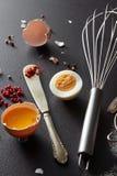Het ruwe en gekookte ei, een metaal zwaait en een mes met Spaanse peper op een zwarte concrete achtergrond voorbereiding royalty-vrije stock afbeelding