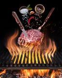 Het ruwe Lapje vlees koken Conceptueel beeld Lapje vlees met kruiden en bestek onder brandende grillrooster royalty-vrije stock foto's