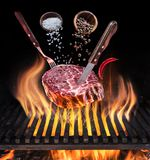 Het ruwe Lapje vlees koken Conceptueel beeld Lapje vlees met kruiden en bestek onder brandende grillrooster stock afbeelding