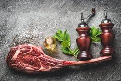 Het ruwe lapje vlees van het tomahawkrundvlees met specerij, zout en peperschudbekers of molen en verse kruiden op donkere rustie royalty-vrije stock foto