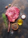 Het ruwe lapje vlees van het Riboog of het rundvleeslapje vlees op het grafiet scheept met kruiden en kruiden in stock fotografie