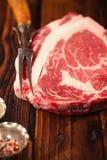 Het ruwe lapje vlees van rundvleesribeye op houten lijst Stock Afbeelding