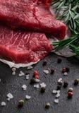 Het ruwe rundvleeslapje vlees met rozemarijn vertakt zich op perkamentdocument met peper en zout stock foto's