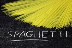 Het ruwe spaghetti en krijt van letters voorzien op donkere bordbackgro Royalty-vrije Stock Foto's