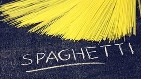 Het ruwe spaghetti en krijt van letters voorzien op donkere bordbackgro Royalty-vrije Stock Afbeeldingen