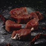 Het ruwe vlees van varkensvleesmedalions Verse lapjes vlees op zwarte achtergrond 45 graad stock fotografie