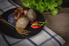 Het sagovarkensvlees in cirkel zwarte plaat met het gebraden knoflook toping heeft het achtereind van de slaplaats en gouden vork stock fotografie