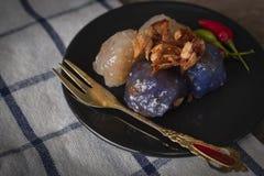 Het sagovarkensvlees in cirkel zwarte plaat met het gebraden knoflook toping heeft Spaanse pepers en gouden vorkplaats op de zwar stock fotografie