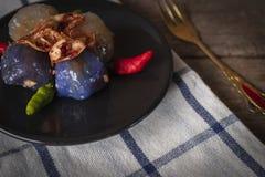 Het sagovarkensvlees in cirkel zwarte plaat met het gebraden knoflook toping heeft Spaanse pepersplaats op zwarte plaat en gouden royalty-vrije stock afbeelding