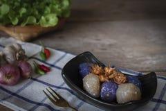 Het sagovarkensvlees in zwarte plaat met het gebraden knoflook toping heeft Spaanse pepers, Sjalot, de linkerhand van de knoflook stock foto's