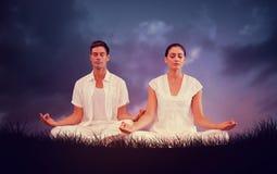 Het samengestelde beeld van aantrekkelijk paar in wit die in lotusbloem mediteren stelt Stock Afbeeldingen