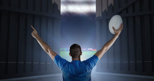 Het samengestelde beeld van achtermening van de holdingsbal van de rugbyspeler met wapens hief 3d op Royalty-vrije Stock Foto's