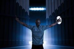 Het samengestelde beeld van achtermening van sportman met wapens hief 3d op de bal van het holdingsrugby Royalty-vrije Stock Afbeeldingen
