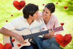 Het samengestelde beeld van de mens en zijn vriend bekijken elkaar terwijl hij de gitaar speelt Stock Afbeeldingen