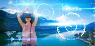 Het samengestelde beeld van jonge vrouw met wapens hief het kijken door virtuele werkelijkheidssimulator op royalty-vrije stock afbeeldingen