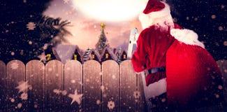 Het samengestelde beeld van santa voert een ladder op stock foto