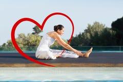 Het samengestelde beeld van vreedzaam brunette in de yoga van janusirsasana stelt poolside Royalty-vrije Stock Afbeeldingen